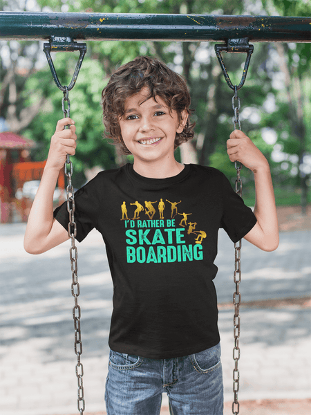 Kid standing on a swing wearing T-shirt with I'D  Rather Be Skate Boarding design available from the Xpert Apparel Store