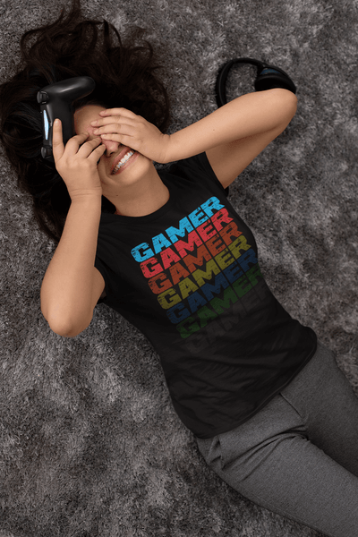 Girl playing Video game laying on floor with hands over face wearing black T-shirt with Faded Out Gamer Design from the Xpert Apparel Store
