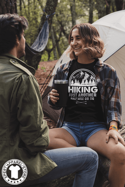 "Woman Sitting on log outside her tent with a  friend wearing a flannel shirt and black t-shirt with ""Hiking, just another half mile or so"" design on the front. available from the Xpert Apparel Store."