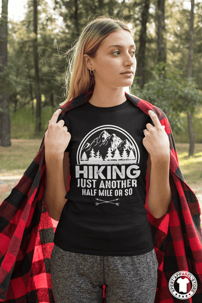 "Young Woman Standing in the Park with a red and black ""flannel blanket"" and wearing a black t-shirt with ""Hiking, just another half mile or so"" design on the front. available from the Xpert Apparel Store."