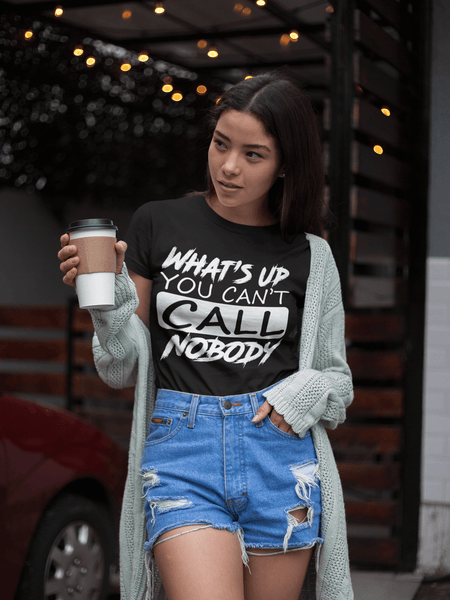 "Beautiful young lady holding cup of coffee wearing blue jeans shorts and Black T-shirt with ""Whats's up you can't call nobody now available from the Xpert Apparel Store"
