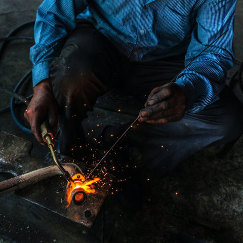 man using torch to weld pipe