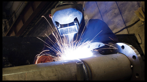 Man welding with auto-darkening helmet
