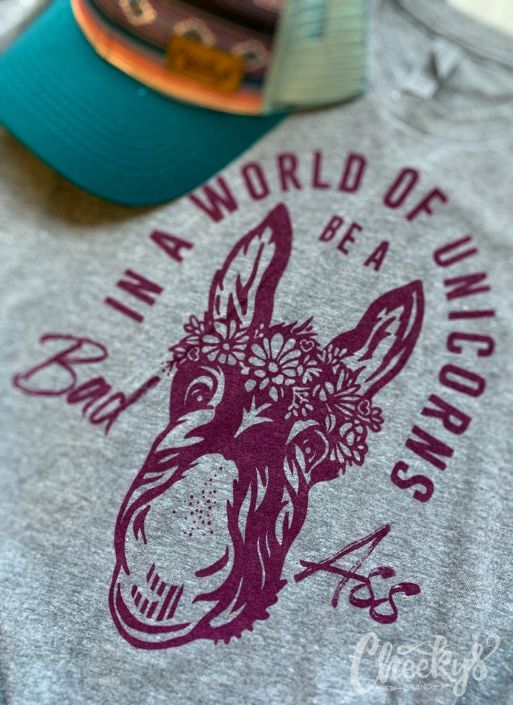 In a World of Unicorns Be A Bad Ass Unisex Tee in Gravel Road