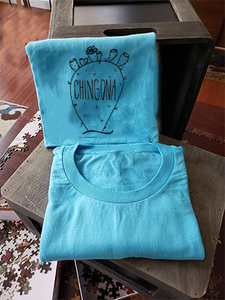 "Our blue tee with a nopal that reads ""chingona"". The tee is folded and propped up on a box."