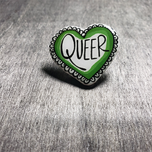 "Load image into Gallery viewer, The pin is heart shaped and says the word ""Queer"" in the center. The color is blue"
