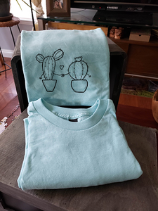 A closeup of our cacti holding hands on a light blue t-shirt. They are folded and leaning against a box.