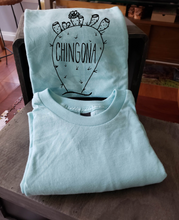 "Load image into Gallery viewer, Our sky blue tee with a nopal that reads ""chingona"". The tee is folded and propped up on a box."