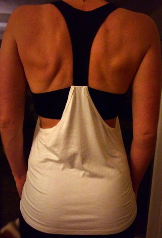 white and black ladies gym vest with racer back detail and attached bra top.
