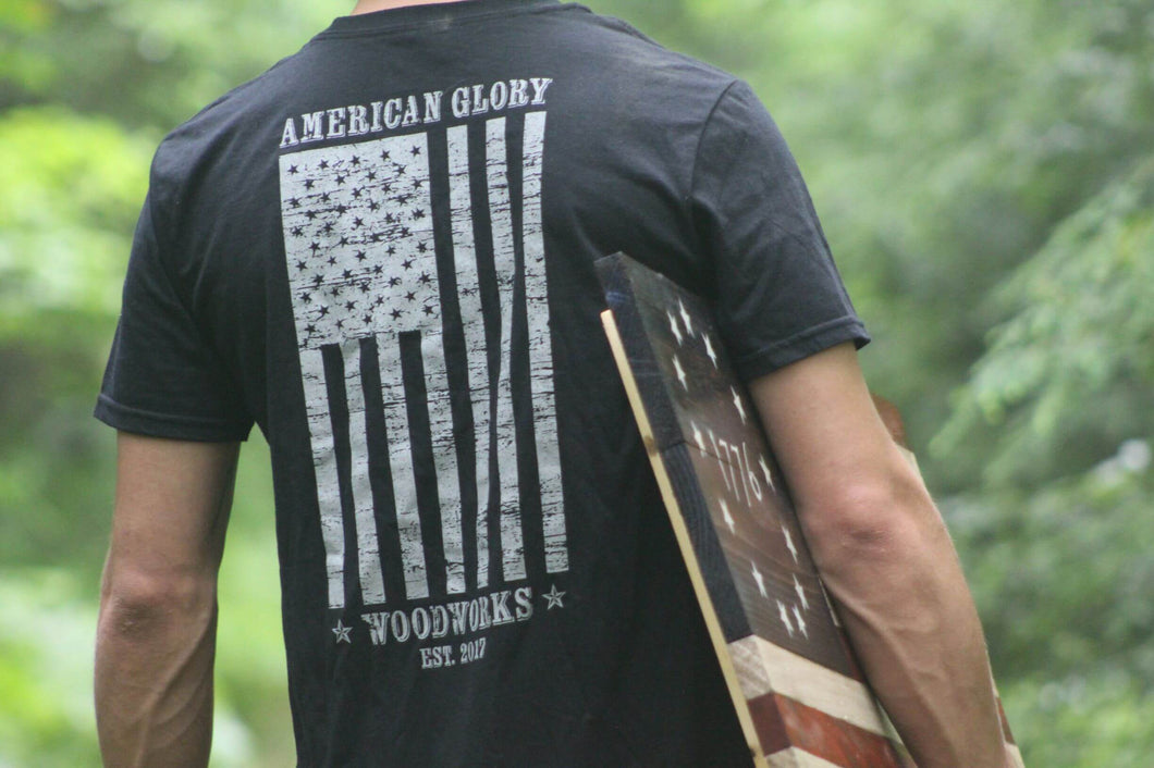 Man wearing American Glory Woodworks t-shirt and holding wooden flag