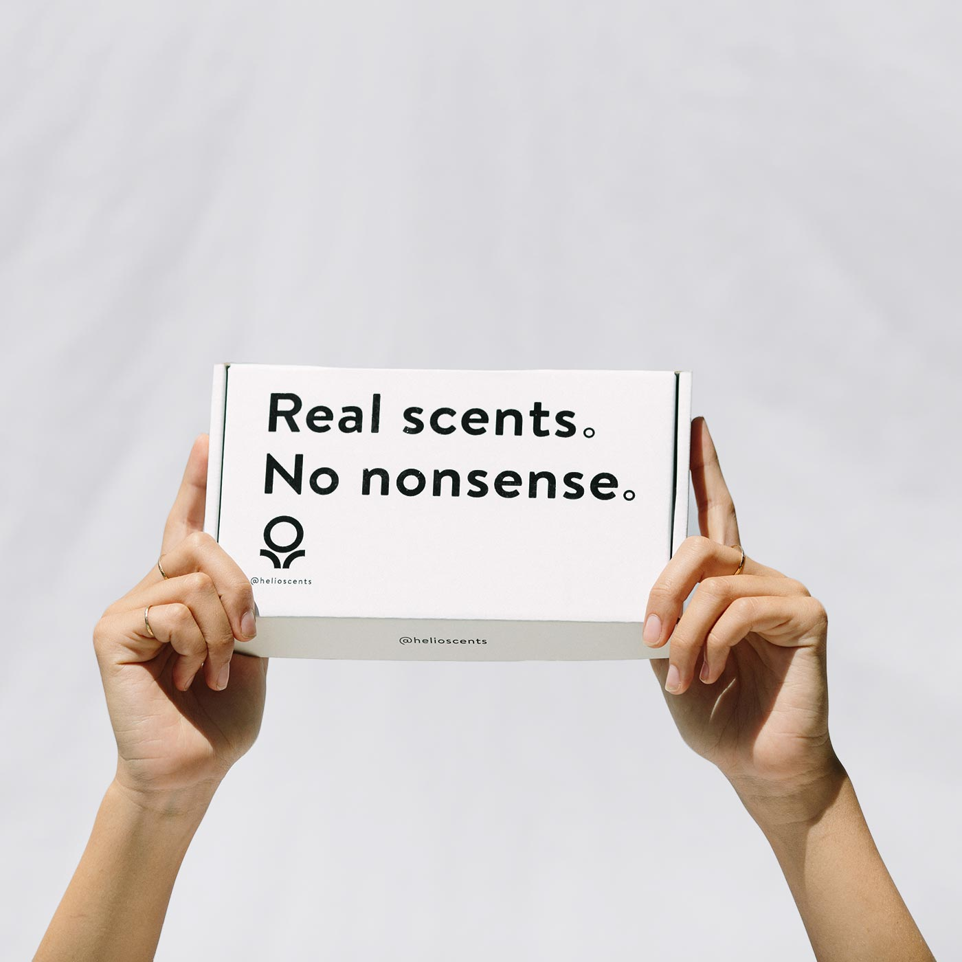 Girl holding box that says Real Scents. No Nonsense