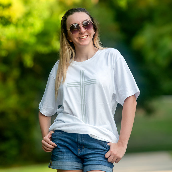 Model wearing white Christian cross t-shirt, denim shorts and sunglasses photographed outside with soft green background