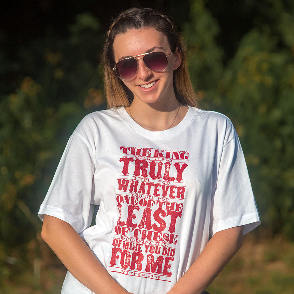 Model wearing Matthew 25:40 in bold, textured design printed in red on white t shirt