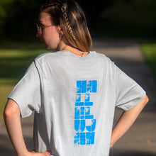 "Load image into Gallery viewer, Woman photographed outdoors with ""Hallelujah God be Praised"" printed in light blue on back of light gray t-shirt."