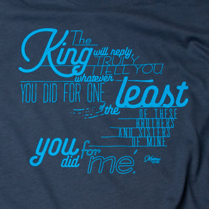 Close up of Matthew 25:40 printed in light blue on navy t shirt