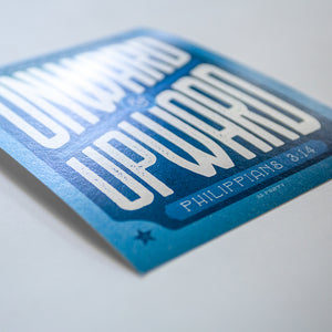 Close up of print with onward and upward and Philippians 3:13 with dynamic blue and white design
