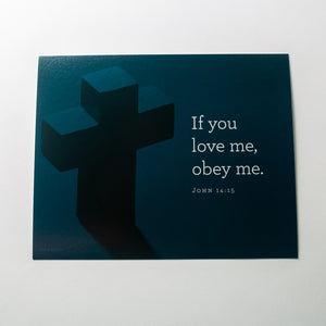 John 14:15, If you love me, obey me. Printed on blue cross background.