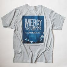 Load image into Gallery viewer, James 2:13, Mercy triumphs over judgement, on blue sky photo on light grey t shirt