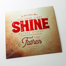Load image into Gallery viewer, Angled shot of Metallic photo print with Matthew 5:16 in textured type with wooden background