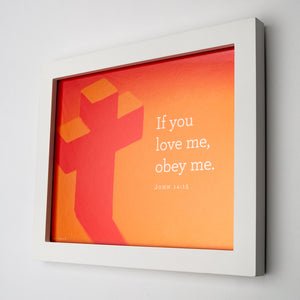 "John 14:15, ""If you love me, obey me."" Printed on orange cross photo in white frame"