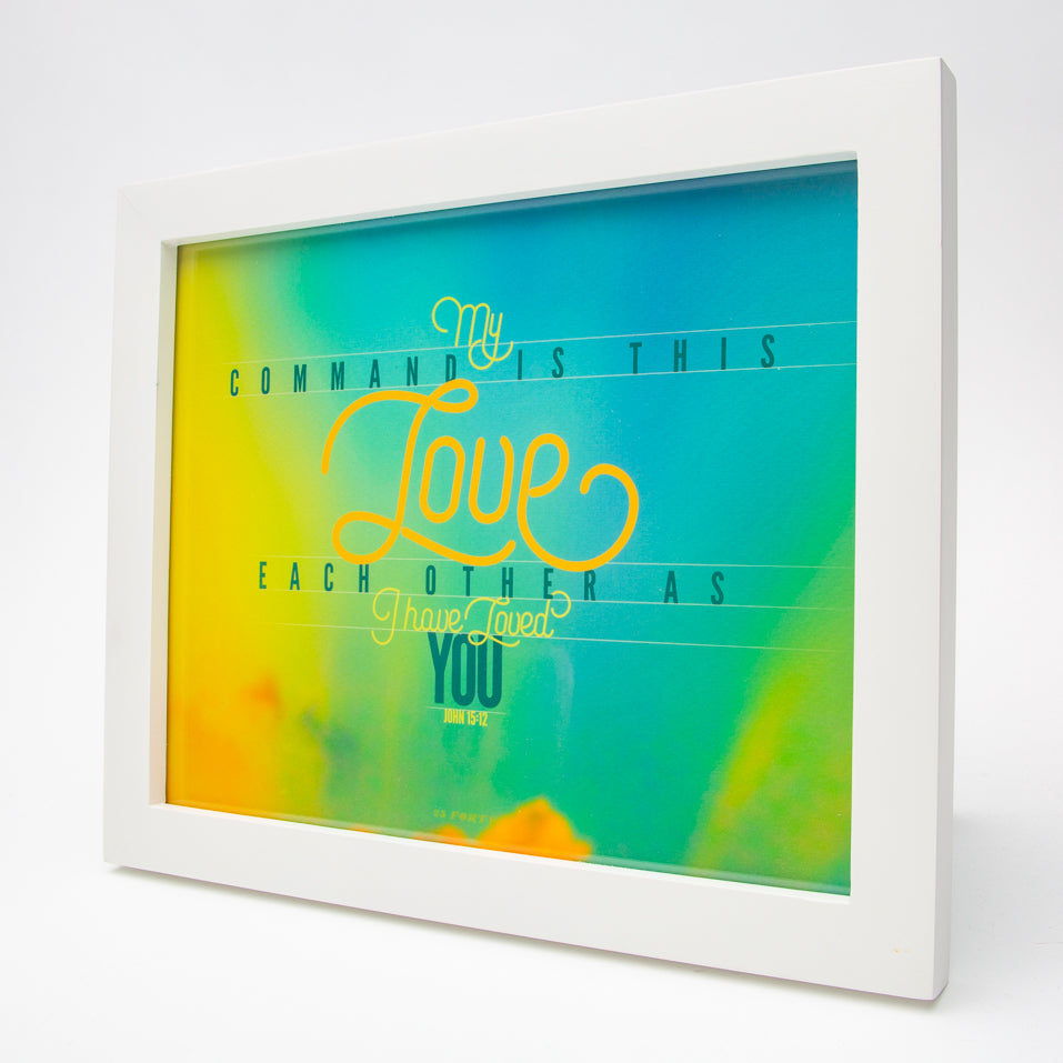 John 15:12 in modern graphics on sunset background in white frame
