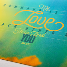 Load image into Gallery viewer, Close up of John 15:12 in modern graphics on sunset background
