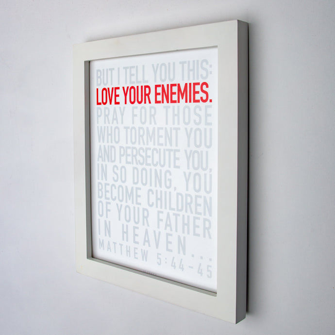 Matthew 5:44-45, Love your enemies in red, other type in gray, on fine art paper in white frame.