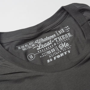 Close up of Matthew 25:40 printed as the tag on a charcoal gray t shirt
