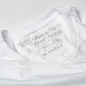 Studio close up photo of collar of white t shirt on white background with Matthew 25:40 printed as the tag