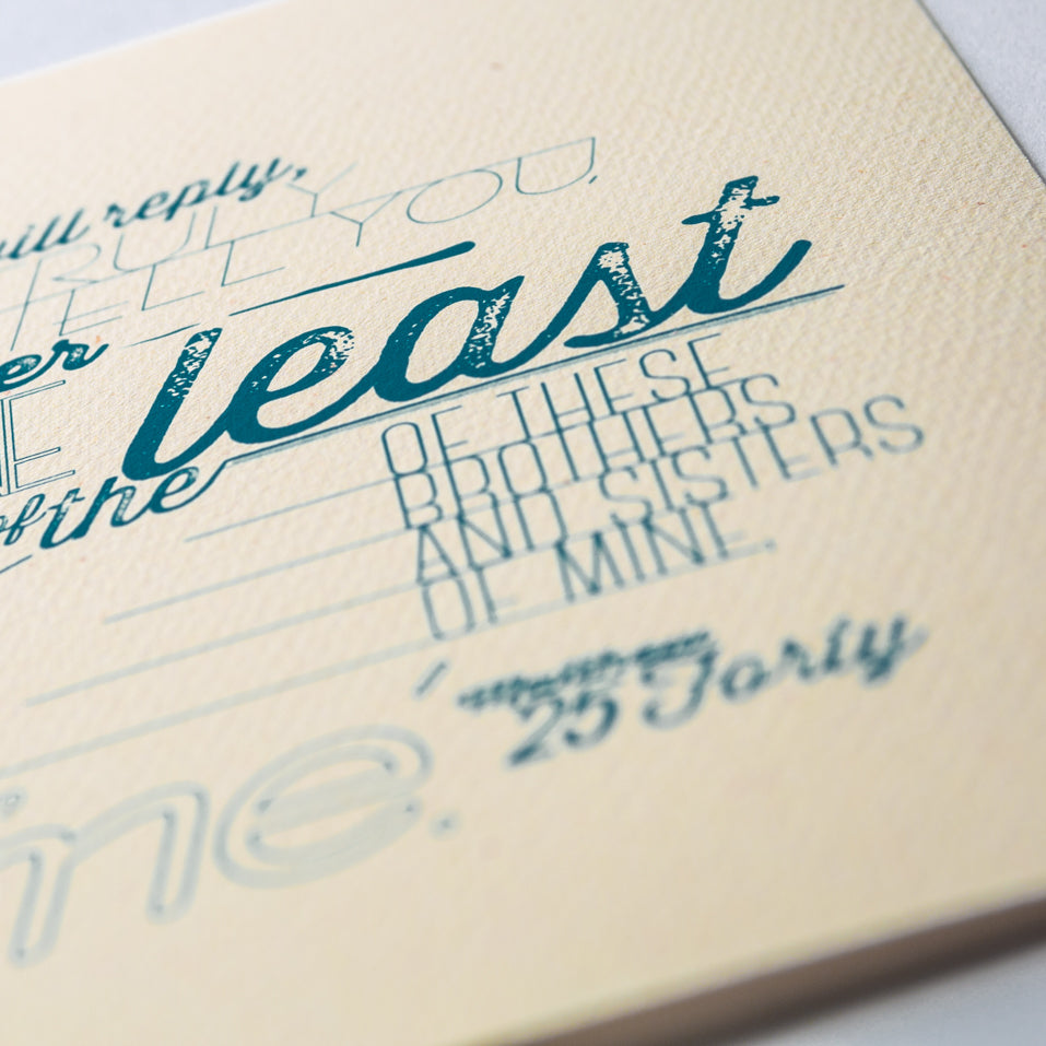 Macro shot of Matthew 25:40 printed in modern, textured design in blue on pale yellow paper.