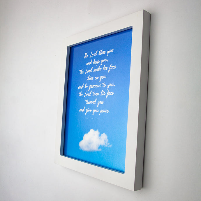 Framed (white) print of  Numbers 6:24-26 in white handwritten script on blue sky with one cloud