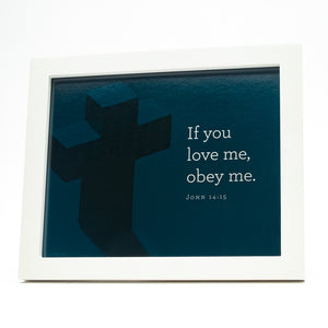 John 14:15, If you love me, obey me. Printed on blue cross background in white frame