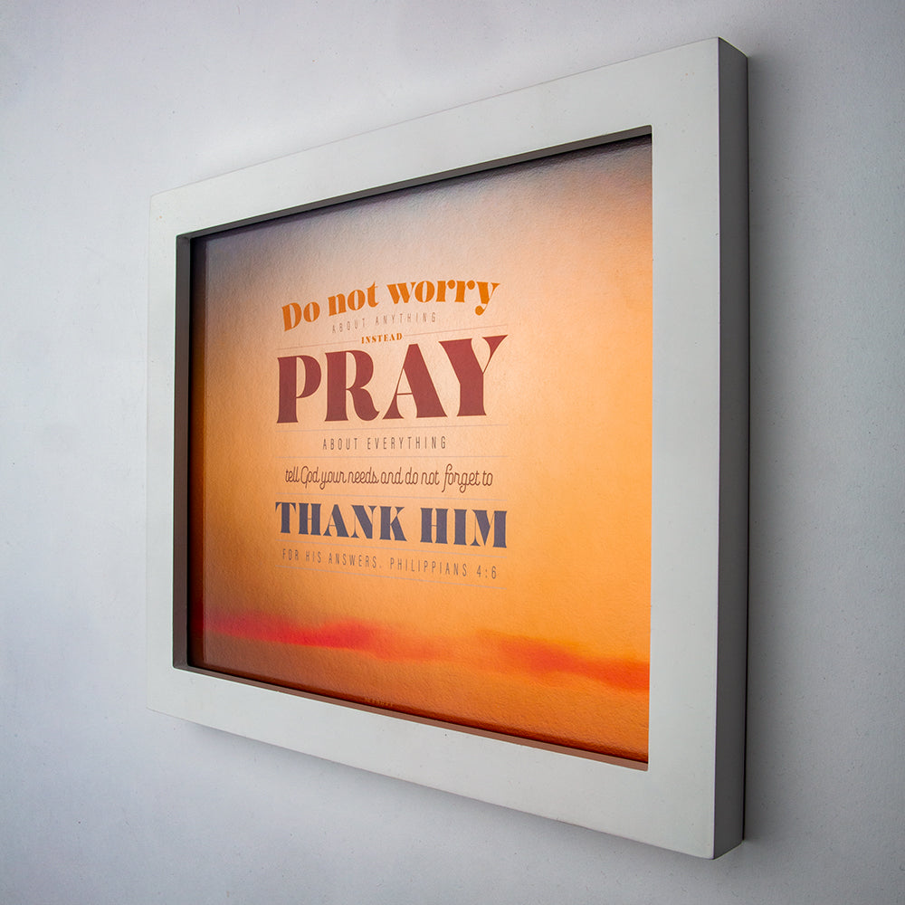 Philippians 4:6 printed in modern fonts and sunset background on fine art paper in white frame.