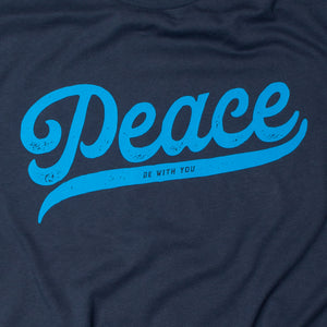 "Close up of Navy blue t shirt with ""Peace be with you""  in script on light blue on the front"