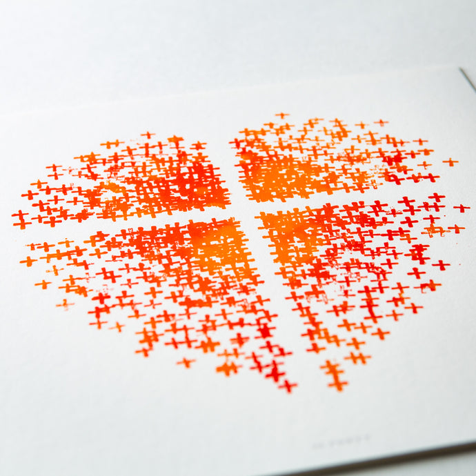 Close up of Orange and red heart made up of crosses with a white cross in the middle on white paper.