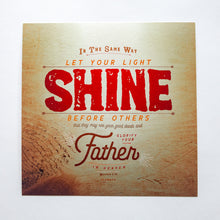 Load image into Gallery viewer, Metallic photo print with Matthew 5:16 in textured type with wooden background