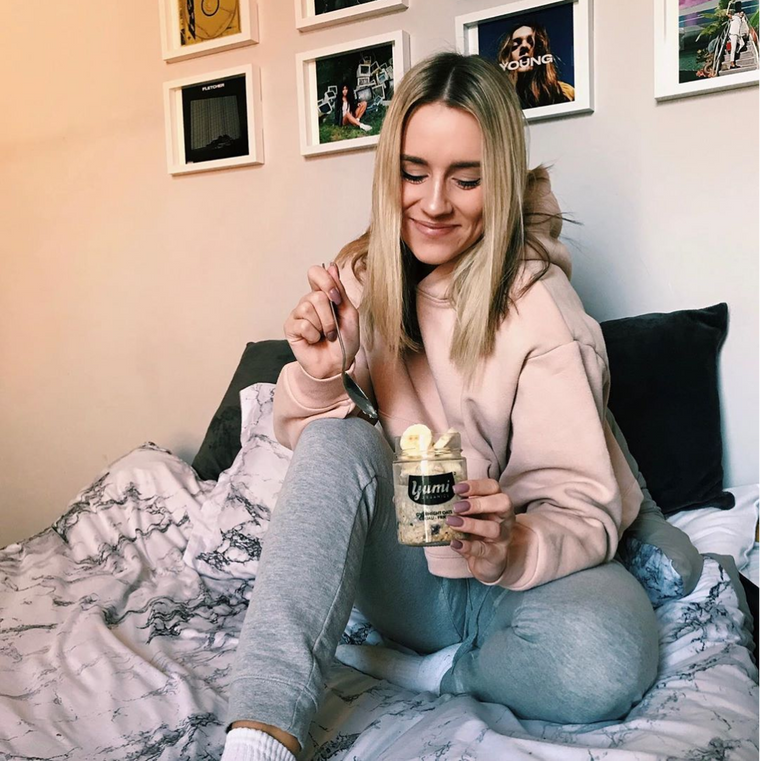 Girl eating yumi overnight oats on bed