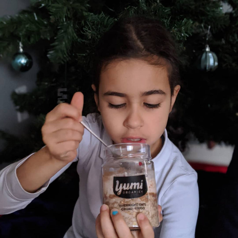little girl eating yumi overnight oats in front of tree