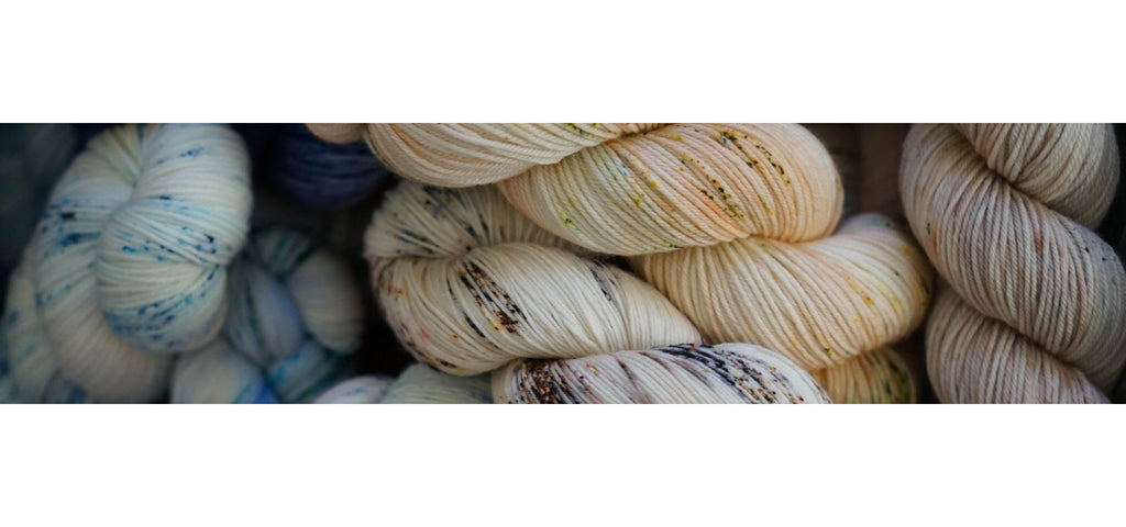 Hand dyed skeins of yarns with blue, yellow, gold, brown speckles close up