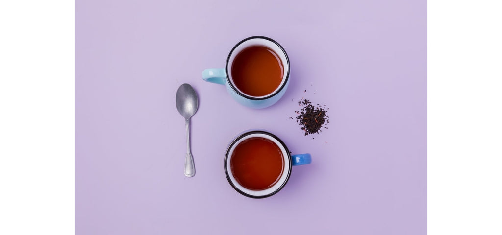 overhead photo of two cups of tea with a spoon to their left and some loose tea leaves to their right on a blue white background