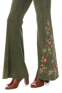 Close up of floral embroidery on olive green yoga pants bell bottom.