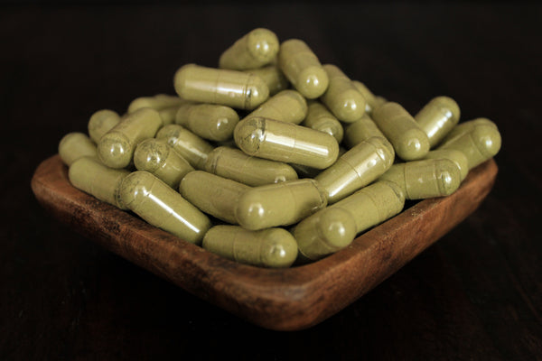 Green Jongkong powder in 1000 mg gelatin capsules in a wooden bowl