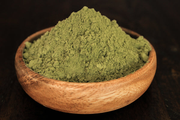 Green Jongkong plant leaf powder shown in wooden bowl