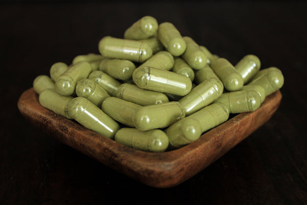 Green maeng da fine leaf powder in 1000 mg gelatin capsules shown in a wooden bowl