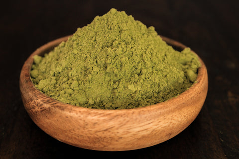 Green Hulu plant powder from indo shown fresh in wooden bowl