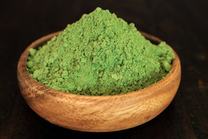 Fresh raw moringa powder in highest quality shown in a wooden bowl