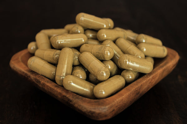 Natural red borneo fresh leaf powder in 1000 mg gelatin capsules presented in a wooden bowl