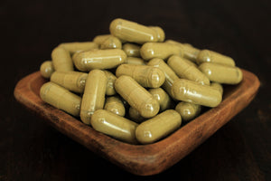 Super Red leaf powder in 1000 mg  gelatin capsules in a wooden bowl for close up