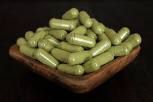 Super white powder in 1000 mg capsules in a wooden bowl close up