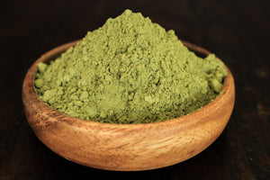 Super white kratom leaf powder finely blended shown in a wooden bowl close up